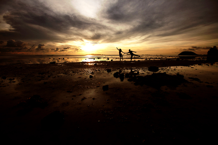 A pair of young people are having fun running on the beach at sunset. Imagens