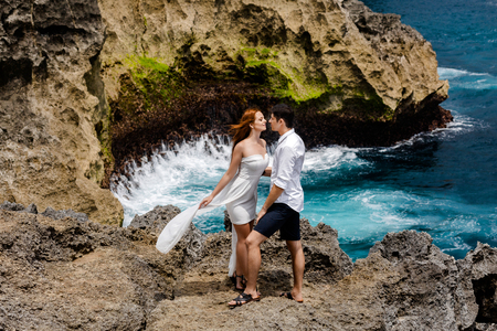A beautiful girl and a guy on a cliff near the sea look at each other sensually. Stock Photo