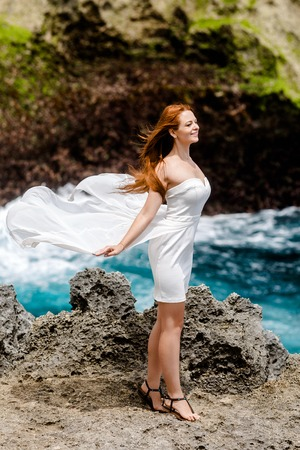 A young girl in a white dress is standing on a rock near the sea. Dress girls fluttering in the wind. The girl smiles, hands drawn back Stockfoto