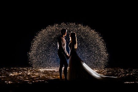 Bride and groom on the night beach against the background of a glowing sand sphere