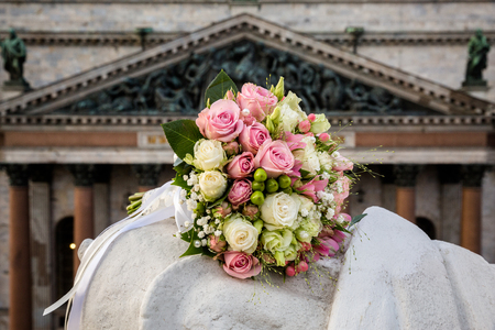 Buds of pink and white roses in a wedding bouquet on the background of the cathedral Stockfoto