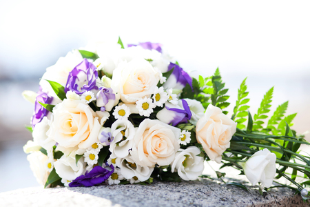 Rosebuds and eustoma in combination with a field chamomile in a refined wedding bouquet on a granite surface 版權商用圖片