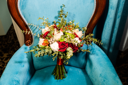 Beautiful wedding bouquet of white and red roses on the background of blue armchair 版權商用圖片