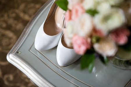 Brides shoes on a blurred background of a wedding bouquet