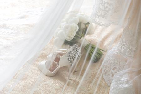 Hochzeitsstrauß neben den Brautschuhen hinter dem Schleier