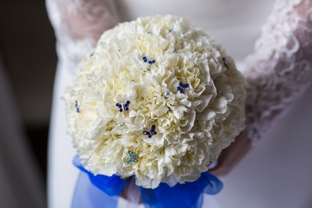 Unrecognizable bride holding a refined wedding bouquet of white peonies with blue ribbon