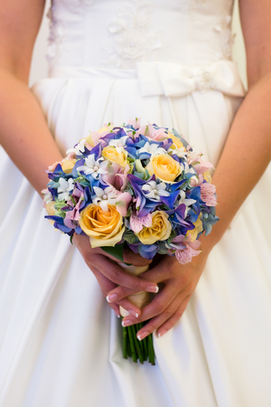 Charming wedding bouquet of yellow roses and blue hydrangea with orchids in the hands of an unrecognizable bride