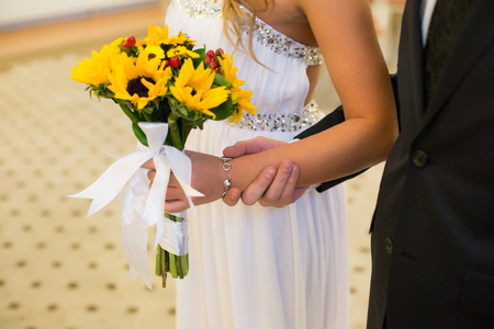 A miniature bouquet of flowers of a sunflower, supplemented with red hypericum berries, in the hands of an unrecognizable bride and groom 版權商用圖片