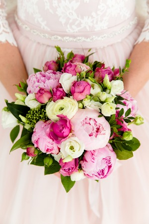 Unrecognizable bride holding a refined wedding bouquet of pink roses and peonies with white eusmoy 版權商用圖片