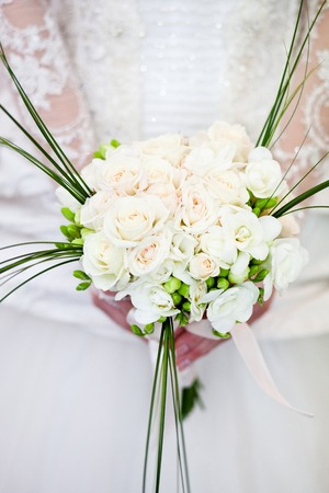 Exquisite wedding bouquet of white flowers of roses and freesia in the hands of an unrecognizable bride 版權商用圖片