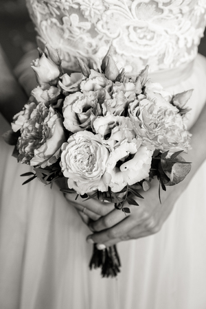 An unrecognizable bride is holding a refined wedding bouquet of white and pink roses with eustoma, in black and white