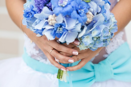 Unrecognizable bride holding a refined wedding bouquet of blue hydrangea Фото со стока - 122942862