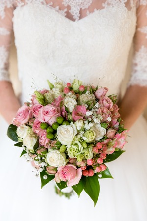 Romantic bouquet of pink and white roses in the hands of an unrecognizable bride