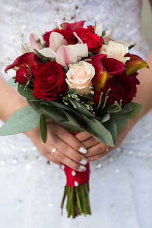 Charming wedding bouquet of pink and red roses in the hands of an unrecognizable bride