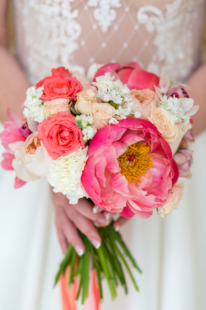 Unrecognizable bride holding a refined wedding bouquet of pink and red roses with peonies 版權商用圖片