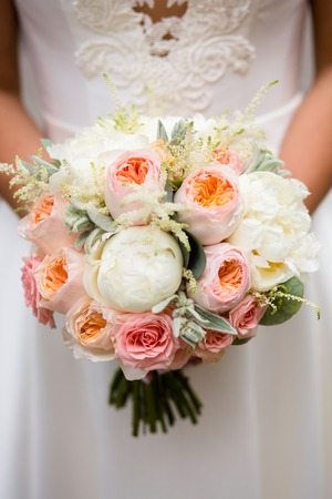 Wedding bouquet of white and cream peonies in the hands of the bride