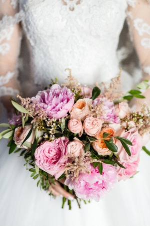Beautiful bridal bouquet of peonies and pink roses in the hands of an unrecognizable bride 版權商用圖片