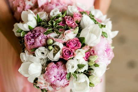Unrecognizable bride holding a refined wedding bouquet of pink roses and peonies with white eusmoy and tulips