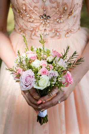 Romantic bouquet of pink, white and gray roses in the hands of an unrecognizable bride