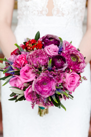 Exquisite bouquet of red and pink roses and peonies in the hands of the bride