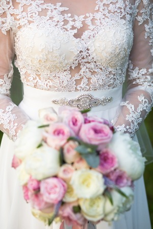 Unrecognizable bride holding a refined wedding bouquet of pink and white roses with peonies