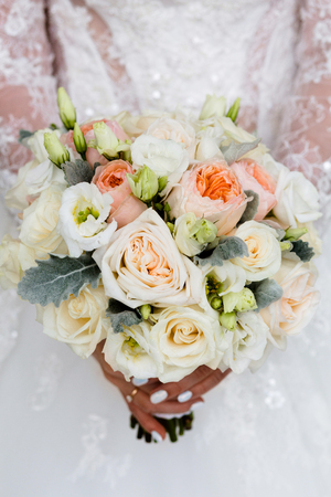 Unrecognizable bride holding a refined wedding bouquet of white roses and peonies with a freesia