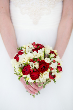 Unrecognizable bride holding a refined wedding bouquet of red roses and white freesias