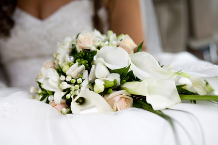 Buds of cream roses combined with white calla and freesia in a wedding bouquet on a blurred background of the bride 版權商用圖片