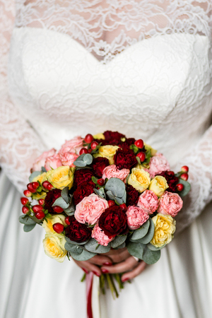 Luxurious bouquet of pink, red and yellow roses in the hands of an unrecognizable bride 版權商用圖片