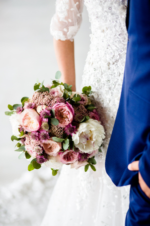 Wedding bouquet of roses and peonies on the background of a young couple 版權商用圖片
