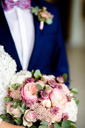 Hochzeitsstrauß aus Rosen und Pfingstrosen auf dem Hintergrund eines jungen Paares