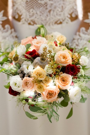 Luxurious bouquet of beige, cream and red roses with snow-white freesia in the hands of an unrecognizable bride