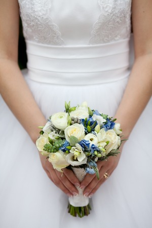 Charming wedding bouquet of white roses and freesias with blue flowers in the hands of an unrecognizable bride