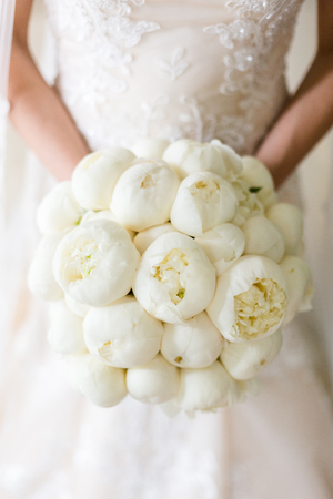 Buds of snow-white peonies in a wedding bouquet, in the hands of an unrecognizable bride 写真素材