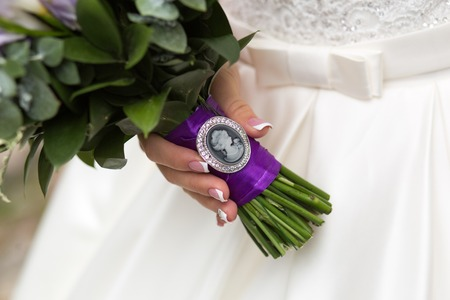 Brooch-pendant cameo princess on a wedding bouquet in the hands of the bride Фото со стока
