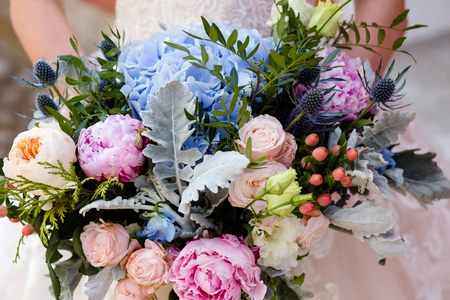 Wedding bouquet of different flowers in the hands of an unrecognizable bride.