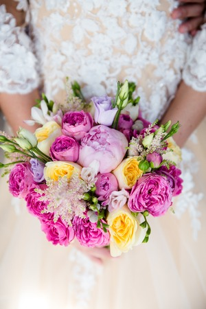Unrecognizable bride holding a refined wedding bouquet of pink and yellow roses with peonies