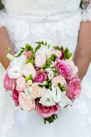 A beautiful bridal bouquet of freesia and pink roses in the hands of an unrecognizable bride