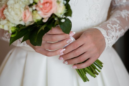 Wedding bouquet of pink roses and white freesias in the hands of the bride