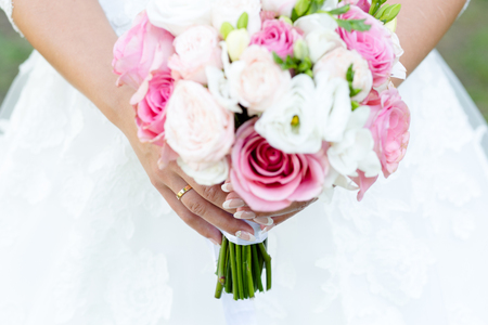Wedding bouquet of pink roses and white peonies with freesias in the hands of an unrecognizable bride