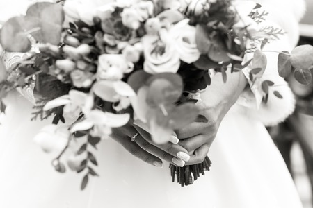 Exquisite wedding bouquet in the hands of an unrecognizable bride, black and white shot Фото со стока