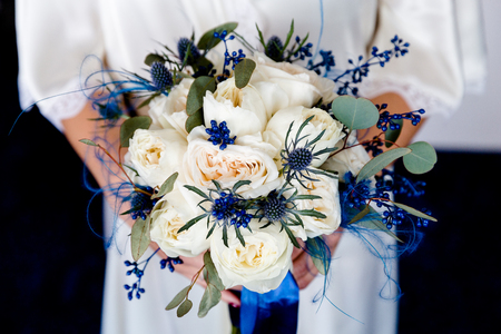 Bouquet of white roses with blue flowers in the hands of the bride 版權商用圖片