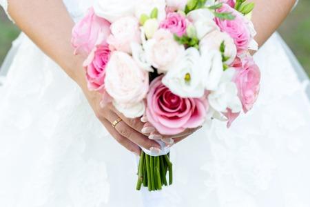 Bruidsboeket rozen en fresia's in de handen van de bruid