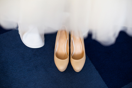 Cream womens shoes on a blue carpet, in the foreground a blurred hem of a wedding dress