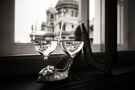 A pair of glasses of wine and women's shoes on the windowsill, St. Isaac's Cathedral is visible through the window on a blurred background Stock Photo