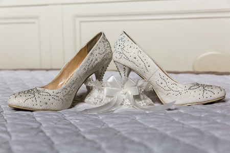 White female shoes of the bride with pastes and garter on a bedspread