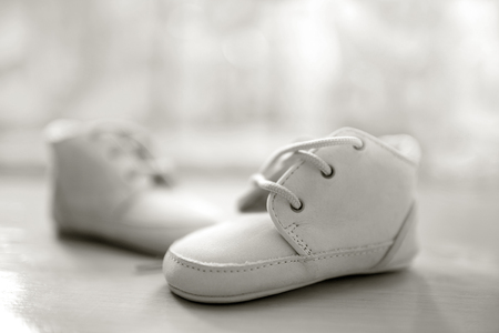 White baby booties made of leather. Shallow depth of field, closeup