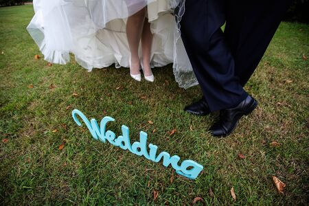 Legs of the groom in black shoes and brides in white heels with a snow-white hem of a wedding dress on green grass, next to the letters wedding.