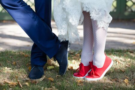 Bride in red shoes with lacing and stockings with a snow-white hem of a wedding dress on the grass. Legs of the groom in blue shoes and trousers.