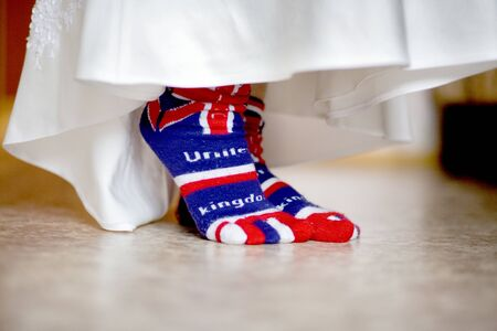 The legs of the bride and the hem of a wedding dress in socks with a British flag. British flag socks